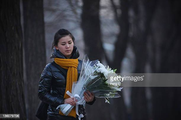 North Korean man holding flowers arrives at the North Korea embassy to mourn the death of North Korean leader Kim Jongil on December 19 2011 in...