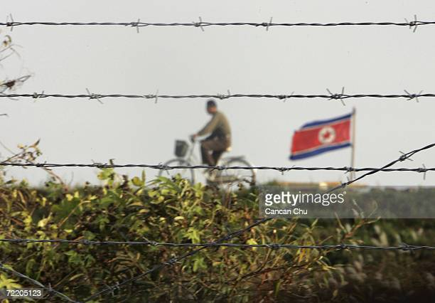 North Korean man riding a bicycle near a North Korean flag is seen through the newly installed fence by the Chinese side in this picture taken on...