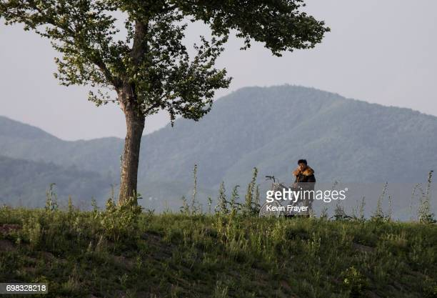 North Korean man sits on his bicycle on the Yalu river north of the border city of Sinuiju, North Korea across from Dandong, Liaoning province,...