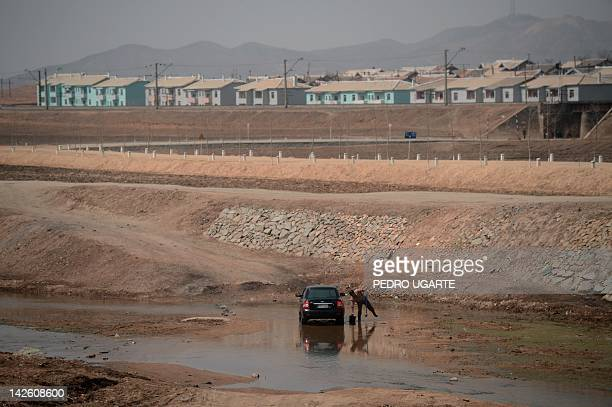 A North Korean man washing his car is seen from the window of a train along the railway line between Pyongyang and the North Phyongan Province on the...