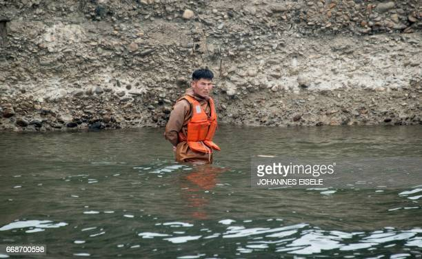 A North Korean man wears a life vest as he stands in the Yalu river near Sinuiju opposite the Chinese border city of Dandong on April 15 2017 / AFP...