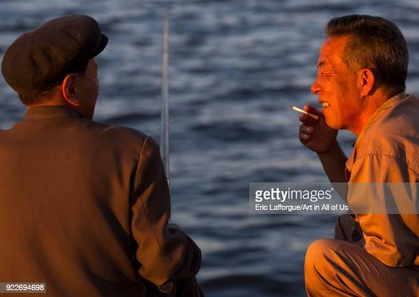 North Korean men fishing and chatting Kangwon Province Wonsan North Korea on September 10 2012 in Wonsan North Korea
