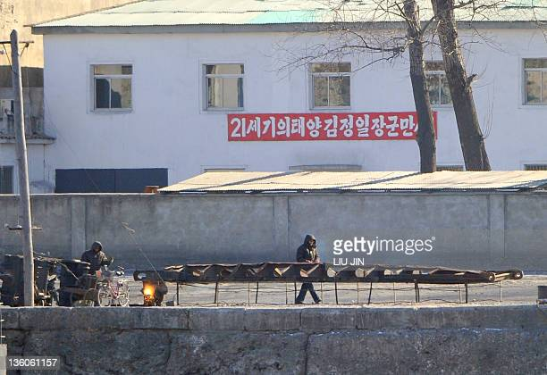North Korean men fix a boat on the bank of the Yalu River in the North Korean town of Sinuiji, on December 22 in this picture taken from the opposite...