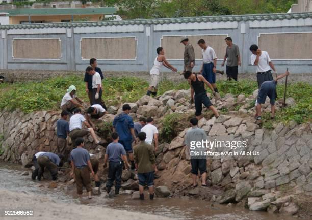 North Korean men repairing the river banks wall after a flood, North Hwanghae Province, Kaesong, North Korea on September 11, 2011 in Kaesong, North...