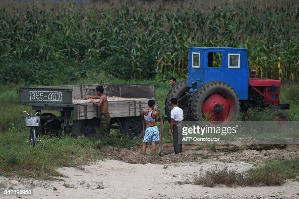 North Korean men unload a trailer on the bank of the Yalu river near the North Korean town of Sinuiju opposite the Chinese border city of Dandong in...