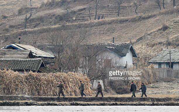 North Korean men walk amid a dry and barren landscape on the banks of the Yalu River some 70 kms north of Dandong in northeast China's Liaoning...