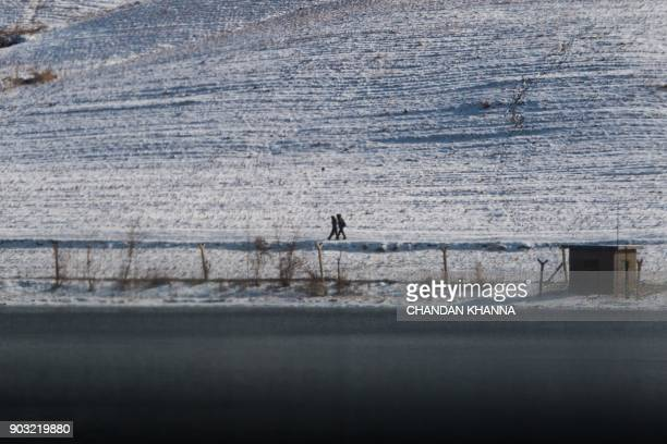 North Korean men walk in North Korea's Sakchu county in North Pyongan province as seen from the Chinese border city of Dandong on January 10 2018 /...