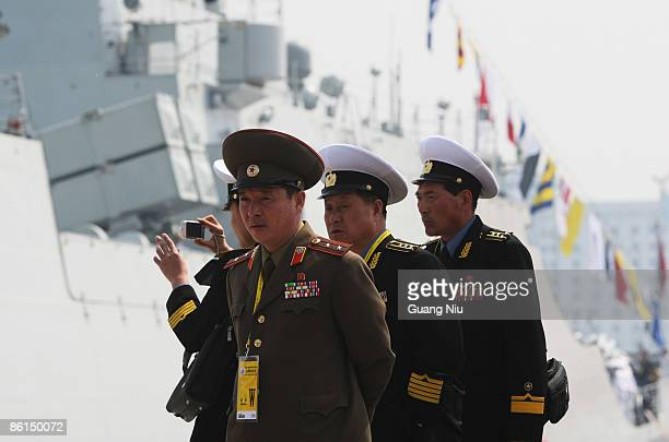 North Korean military officers look at China Navy Battleship of Wenzhou in Qingdao Port on April 22 2009 in Qingdao of Shandong Province China...