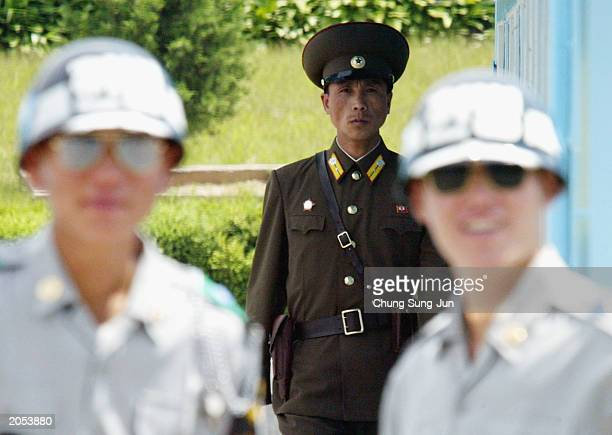 North Korean military soldier looks at South Korean soldiers as he guards the demilitarized zone separating the two Koreas June 4 2003 in the border...
