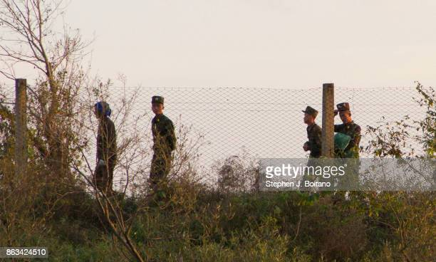 North Korean Military walk the border fence on the Yalu river near the Chinese border