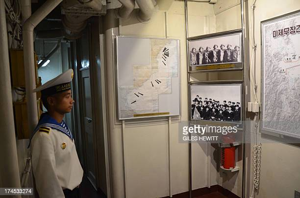 A North Korean navy seaman stands in front of photos and maps displayed aboard the USS Pueblo a US navy technical research ship captured by North...