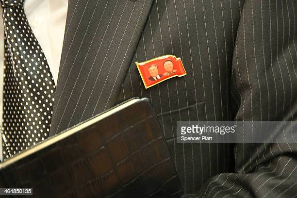 North Korean official wears a pin featuring the faces of Kim Jongun and his grandfather and founder of the current North Korean state Kim Ilsung...