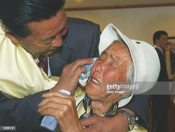 North Korean Oh YooBum wipes tears from his sister Oh MiSaeng of South Korea during a reunion of families from the two countries May 1 2002 at the...