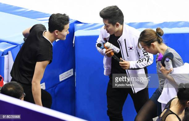 North Korean pair figure skater Kim Ju Sik exchanges words with South Korean pair skaters Kang Chan Kam and Kim Kyu Eun after their practice at the...