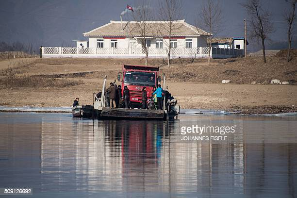 North Korean people and a truck embark on a boat on the Yalu River near the town of Sinuiju across from the Chinese border town of Dandong on...