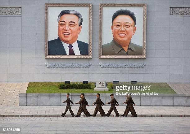 North korean people army soldiers passing in front of kim il sung and kim jong il giant portraits on kim il sung square, pyongyang, North Korea on...