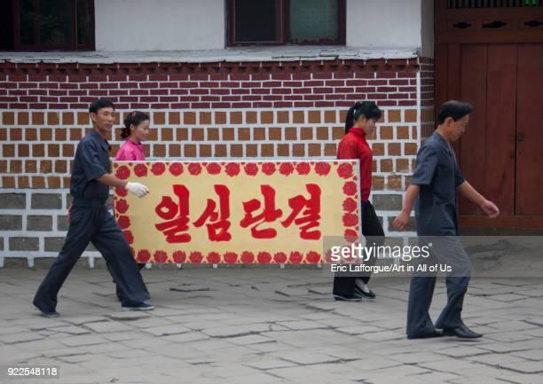 North Korean people carrying a propaganda bilboard i the street North Hwanghae Province Kaesong North Korea on September 11 2011 in Kaesong North...