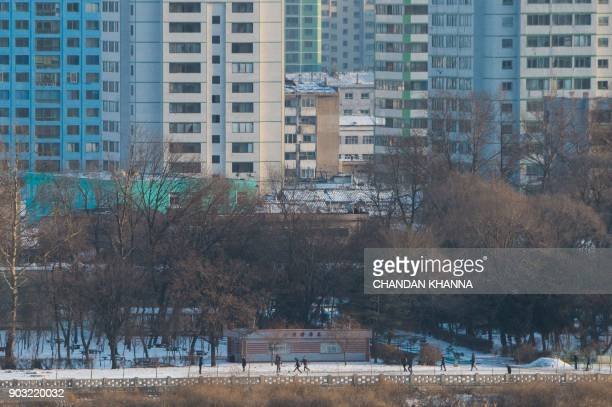 North Korean people play football in the town of Sinuiju as seen from the Chinese border city of Dandong on January 10 2018 / AFP PHOTO / CHANDAN...