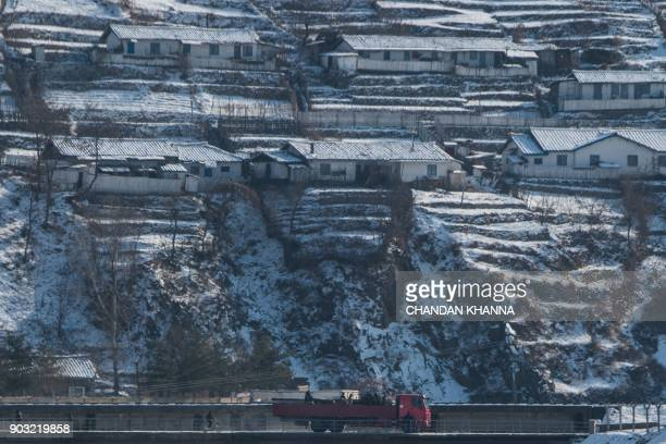North Korean people ride on a truck in North Korea's Sakchu county in North Pyongan province as seen from the Chinese border city of Dandong on...