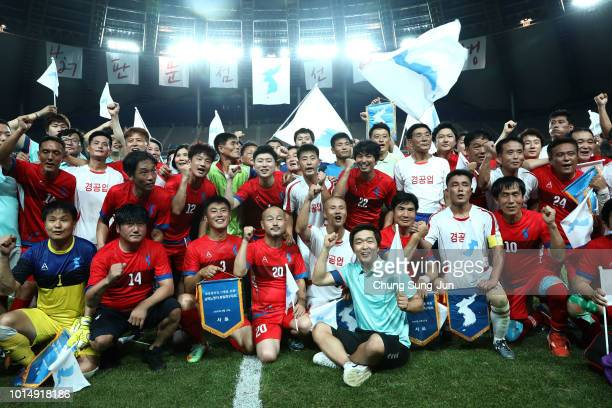"""North Korean players and South Korean players wave the unification flags after the """"Unification Soccer"""" matches at Seoul World Cup stadium on August..."""