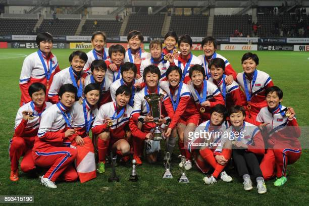 North Korean players pose for photographs as they cerebrate the East Asian Champions at the award ceremony following their 20 victory the EAFF E1...