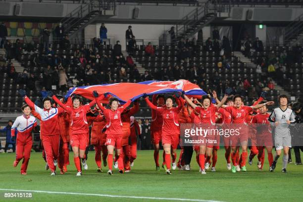 North Korean players run toward supporters with waving a giant national flag as they cerebrate the East Asian Champions at the award ceremony...