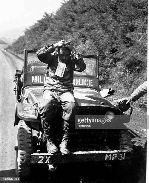 A North Korean prisoner of the US Marines captured when the Marines rolled the enemy back in Naktong River fighting He sits on the hood of an...