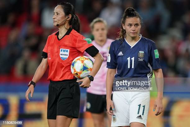 North Korean referee Ri Hyang Ok holds the ball next to Argentina's forward Florencia Bonsegundo prior to a penalty kick for Argentina during the...
