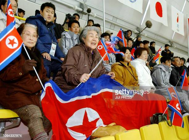 North Korean residents in Japan wave national flags to cheer North Korean women's ice hockey players during their first match against Kazakhstan in...