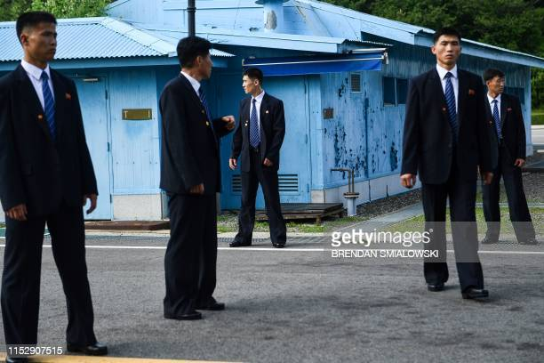 North Korean security agents keep watch south of the Military Demarcation Line that divides North and South Korea as US President Donald Trump and...