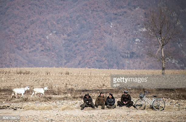 TOPSHOT North Korean shepherds sit by the Yalu River banks near the town of Sinuiju across from the Chinese border town of Dandong on February 9 2016...