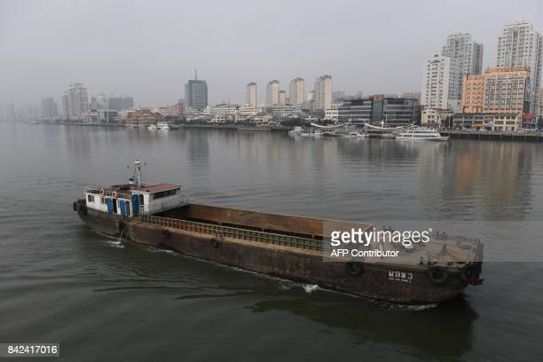 A North Korean ship passes in front of the waterfront of the Chinese border city of Dandong in China's northeast Liaoning province opposite the North...