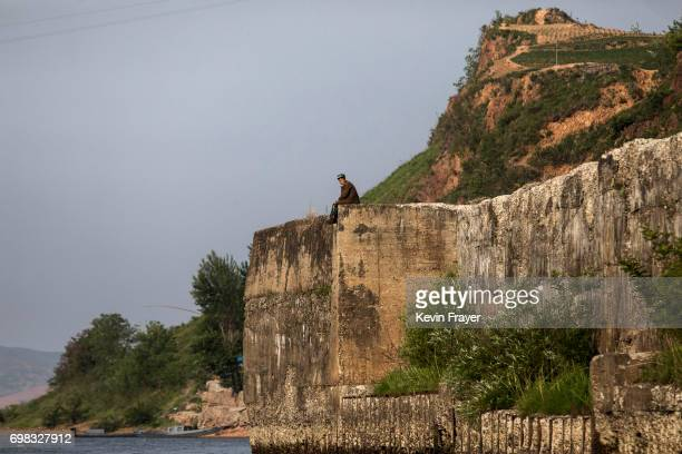 A North Korean sits on a wall on the Yalu river north of the border city of Sinuiju North Korea across from Dandong Liaoning province northern China...