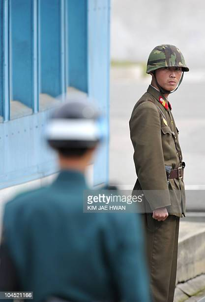 A North Korean soldier and a South Korean soldier stand on duty at the truce village of Panmunjom in the demilitarized zone separating the two Koreas...