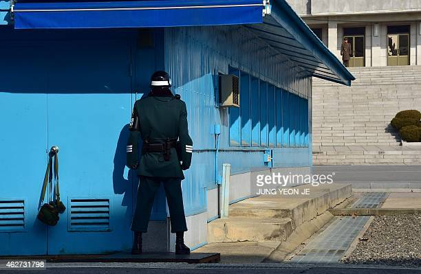 A North Korean soldier and a South Korean soldier stand opposite each other at the truce village of Panmunjom in the Demilitarized Zone dividing the...