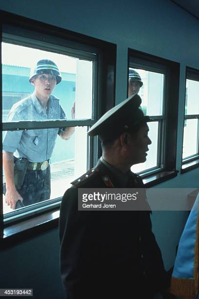 North Korean soldier being observed by American soldiers in Panmunjom on the 38th parallel in the DMZ or demilitarised zone The 25 mile wide 156 mile...