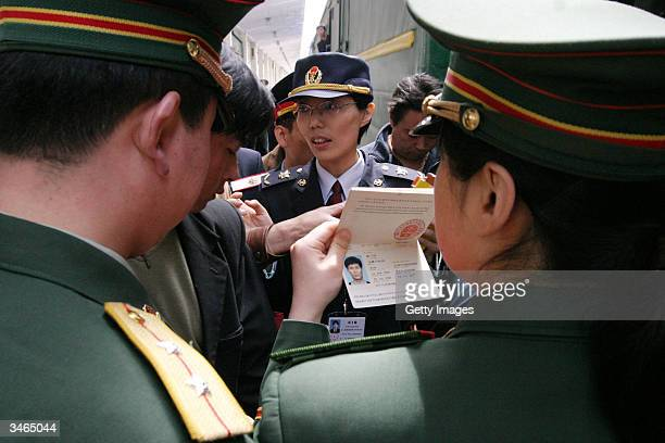 North Korean soldier checks a passenger's passport before the passenger could board a train April 25 2004 bound for Pyongyang in Dandong Liaoning...