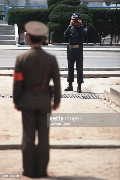 North Korean soldier is being photographed by an American soldier in Panmunjom on the 38th parallel in the DMZ or demilitarised zone The 25 mile wide...