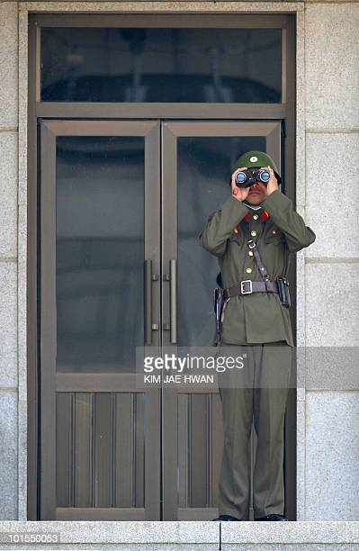 A North Korean soldier keeps watch over the South side wearing a battle helmet at the truce village of Panmunjom in the Demilitarised Zone separating...