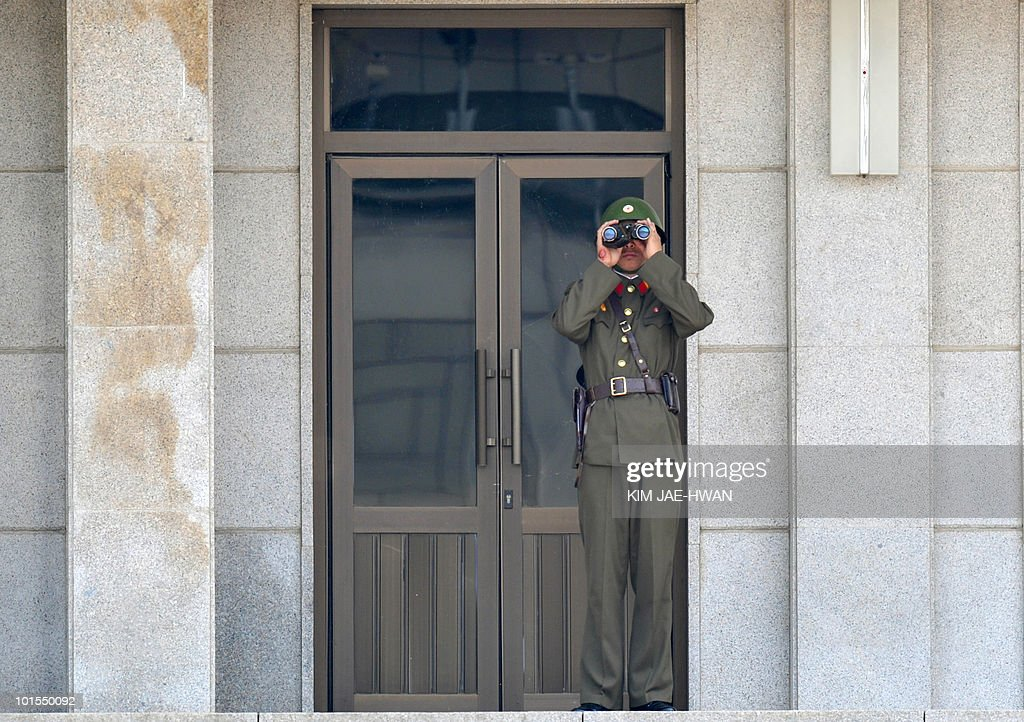 A North Korean soldier keeps watch over the South side wearing a battle helmet at the truce village of Panmunjom in the Demilitarised Zone separating the two Koreas on June 2, 2010. A US aircraft carrier will join a major anti-submarine naval exercise with South Korea next week in a show of strength to North Korea after the sinking of a South Korean warship, reports said.