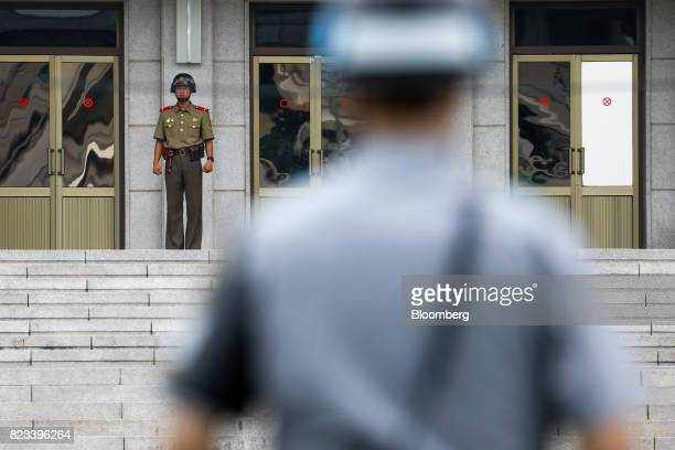 A North Korean soldier left standing guard in front of the Panmungak building looks towards a South Korean soldier at the truce village of Panmunjom...
