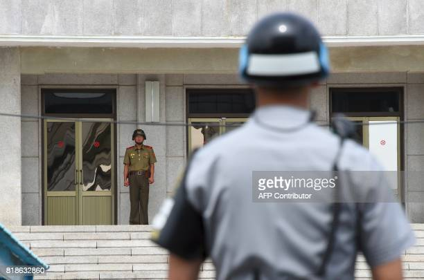 A North Korean soldier looks at the south side as a South Korean soldier stands guard during a press tour to the truce village of Panmunjom in the...