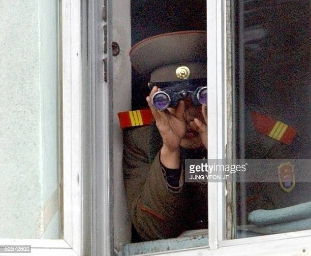 North Korean soldier looks at the South side through binoculars while Hungarian Prime Minister Ferenc Gyurcsany visits the border village of...