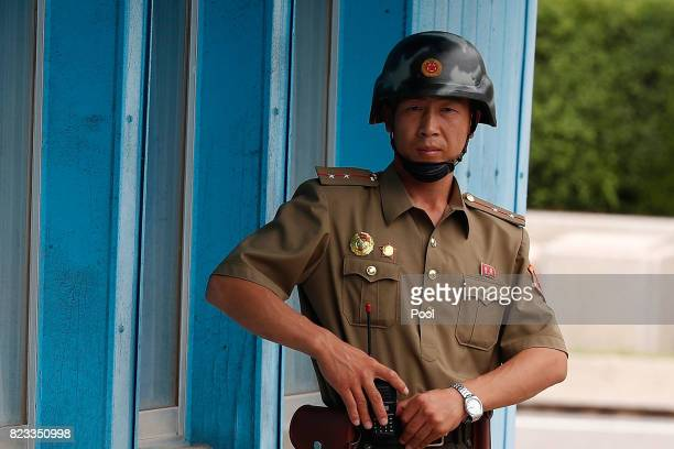 North Korean soldier looks on as South Korean and United Nation officials visit after attending a ceremony to commemorate the 64th Anniversary of the...