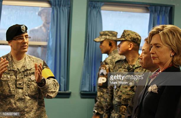 North Korean soldier looks through a window at Secretary of State Hillary Clinton while she visits the UN truce village building that sits on the...