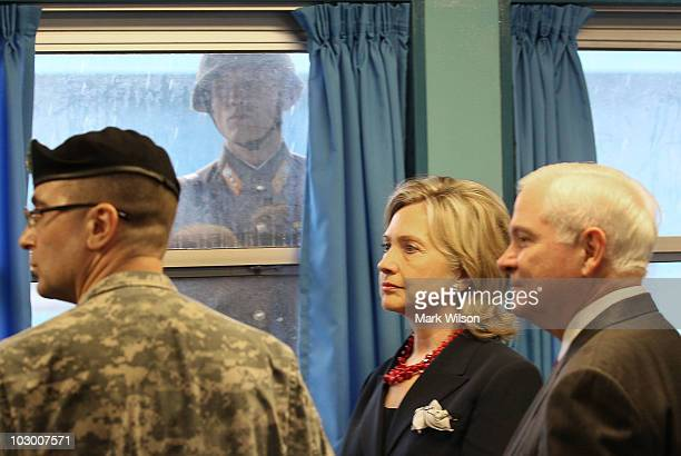 North Korean soldier looks through a window at Secretary of State Hillary Clinton and Secretary of Defense Robert Gates , while they the UN truce...