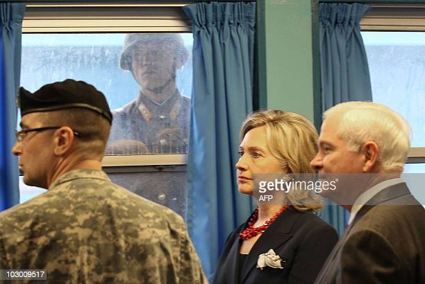 North Korean soldier looks through a window at Secretary of State Hillary Clinton and US Defence Secretary Robert Gates , while at a UN truce village...