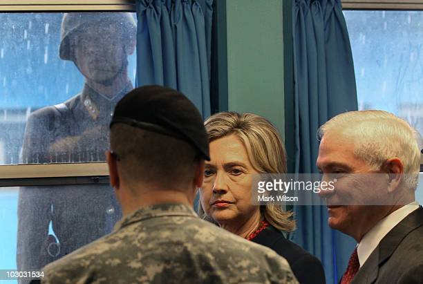 North Korean soldier looks through a window at Secretary of State Hillary Clinton and Secretary of Defense Robert Gates during a visit to UN truce...