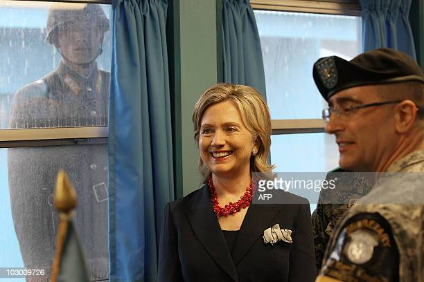 North Korean soldier looks through a window at US Secretary of State Hillary Clinton during a visit at a UN truce village building that sits on the...