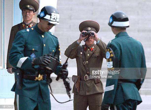 North Korean soldier looks through binoculars to survey across the Demilitarized Zone between two South Korean soldiers at the border village...